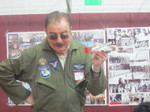 Man giving a speach to the kids in a fighter plane uniform
